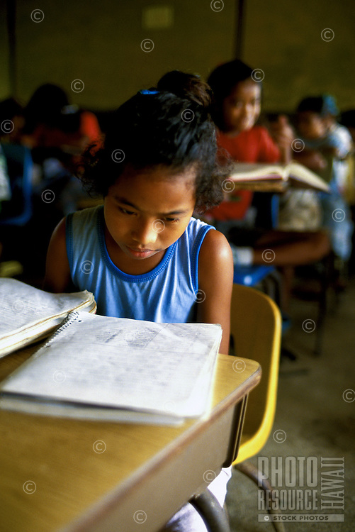 Children studying in school, writing in notebook, in Yap Micronesia.