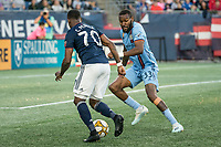 FOXBOROUGH, MA - SEPTEMBER 29: Cristian Penilla #70 of New England Revolution advances on goal as Sebastien Ibeagha #33 of New York City FC comes in to tackle during a game between New York City FC and New England Revolution at Gillettes Stadium on September 29, 2019 in Foxborough, Massachusetts.