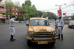 Kolkata police stops a yellow taxi with passenger to find out the reason for moving out of house during 21 days lock down in the country due to covid 19 pandemic. If commuters can not prove a suitable reason they are either sent back to home or being arrested for violating  lock down laws. Kolkata, West Bengal, India. Arindam Mukherjee.