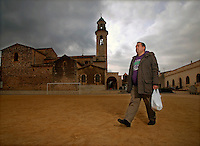 A portrait of Alejandro Cao de Benos, photographed in the village of Salomo in northeast Spain walking across a square past a church. As a Korean-Spanish communist, Alejandro is the president of the Korean Friendship Association (KFA) and has been an advocate of the Democratic People's Republic of Korea (North Korea) since 1990. His Korean name is Zo Sun-il (Korea is One) and he works as an honorary Special Delegate of the DPRK's Committee for Cultural Relations with Foreign Countries - a North Korean government spokesman in Europe.