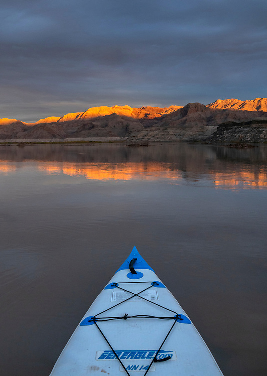 Storm light dances across unnamed mountains near Sandy Point along the Colorado River in the Lake Mead National Recreation Area on the Arizona-Nevada border as viewed from a stand-up paddleboard (Photo from Nevada looking into Arizona)