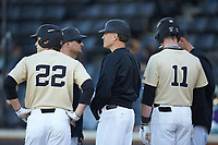Wake Forest Demon Deacons head coach Tom Walter (16) meets with his team during a stoppage in play against the Gardner-Webb Runnin' Bulldogs at David F. Couch Ballpark on February 18, 2018 in  Winston-Salem, North Carolina. The Demon Deacons defeated the Runnin' Bulldogs 8-4 in game one of a double-header.  (Brian Westerholt/Four Seam Images)