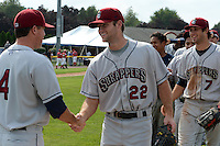 Mahoning Valley Scrappers relief pitcher Kerry Doane (22) shakes hands with coach Shaun Larkin (4) after completing a no-hitter against the Batavia Muckdogs on September 1, 2013 at Dwyer Stadium in Batavia, New York.  Doane went one inning striking out two as the Scrappers pitching duo of Luis Gomez, Carlos Melo, and Doane tossed a no-hitter 6-0 victory over Batavia, Josh McAdams (7) is at right.  (Mike Janes/Four Seam Images)