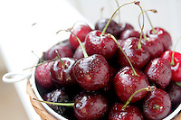 Wet ripe red sweet cherries in a bowl with limited focus.