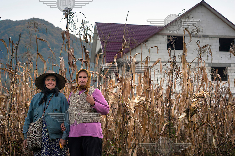 Two elderly women - Ana Timoce and Nastasia Stufoi - pick corn next to a newly constructed building belonging to one of their neighbours who has gone abroad to work in Spain. ..