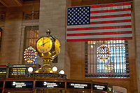 Inside NYC's Grand Central Terminal looking at the clock with the US flag in the background.