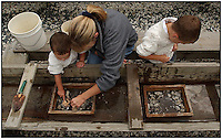 A mother helps her two sons search for gems in the gem mining operations at the Tweetsie Railroad amusement park in the Blue Ridge Mountains between Blowing Rock and Boone, North Carolina. Boys and woman are model released.