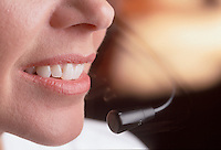 Detail of a smiling woman talking into a telephone headset.