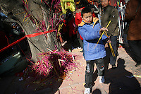 CHINA. A young boy during Chinese New Year in Baiyun Temple in Beijing.  Chinese New Year, or Spring Festival, is the most important festival and holiday in the Chinese calendar In mainland China, many people use this holiday to visit family and friends and also visit local temples to offer prayers to their ancestors. The roots of Chinese New Year lie in combined influences from Buddhism, Taoism, Confucianism, and folk religions.  2008.
