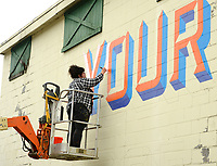 "Artist Olivia Trimble of Fayetteville paints a mural from atop a lift Friday, Sept. 11, 2020, at Southyard in Fayetteville. The mural will read the words ""Love Your Neighbor"" in a design that will also be made available on a T-shirt, the sales from which will be used to help provide food for people in the area who need it. South Yard plans to build a mixed-use structure at the former site of the Farmers Cooperative and wanted to decorate the portion of the building that they are planning to incorporate into the new structure as a way to be a good neighbor. Visit nwaonline.com/200912Daily/ for today's photo gallery. <br /> (NWA Democrat-Gazette/Andy Shupe)"