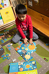 Education preschool 4 year olds boy working on jigsaw puzzle depicting space with illustration on box to guide him