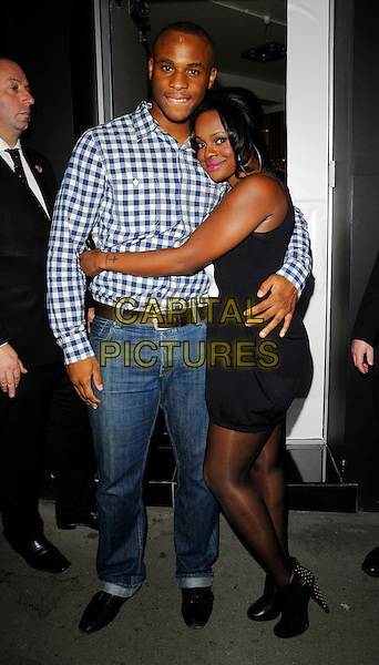 DEAN THOMAS & KEISHA BUCHANAN .The Sugababes new album launch party at JC de Castelbajac boutique, Conduit Street, London, England, .October 9th 2008..full length black and white bib dress studded gold ankle boots tights boyfriend blue and white gingham plaid shirt jeans  hugging .CAP/CAN.©Can Nguyen/Capital Pictures