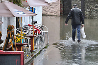 A man walks in a flooded road caused by heavy rain in Crickhowell, south Wales, UK. Saturday 26 October 2019