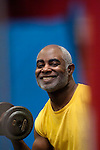 African American man curling weight in gym