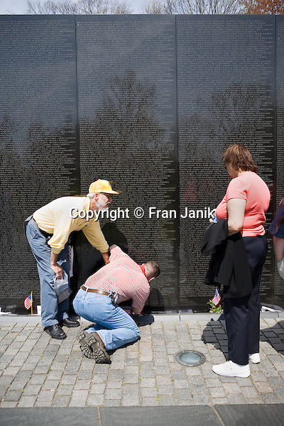 A volunteer at the Vietnam memorial in Washington D.C. assists a visitor in making a rubbing of a name on the wall.
