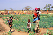 The Gambia. Woman and her five children on their agricultural plot.