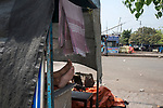 A man rests on his temporary food cart at the largest bus station in Kolkata.  India is going through a 21 days lock down for Corona virus pandemic. Kolkata, West Bengal, India, Arindam Mukherjee.