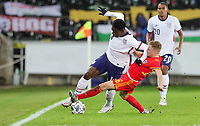 SWANSEA, WALES - NOVEMBER 12: Joe Morrell #16 of Wales slide tackles Owen Otasowie #14 of the United States during a game between Wales and USMNT at Liberty Stadium on November 12, 2020 in Swansea, Wales.