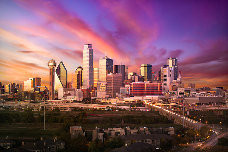 Stock photograph of the Dallas skyline at night/dusk with pink sky and city traffic near Bank of America Plaza and Reunion Tower.
