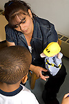 preschool 2-3 year olds female teacher using hand puppet to talk to boy