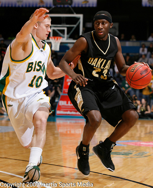SIOUX FALLS, SD - MARCH 10:   Johnathon Jones #23 of Oakland University drives against Ben Woodside #10 of North Dakota State during the Summit League Tournament men's championship game Tuesday evening at the Sioux Falls Arena. (Photo by Dick Carlson/Inertia)