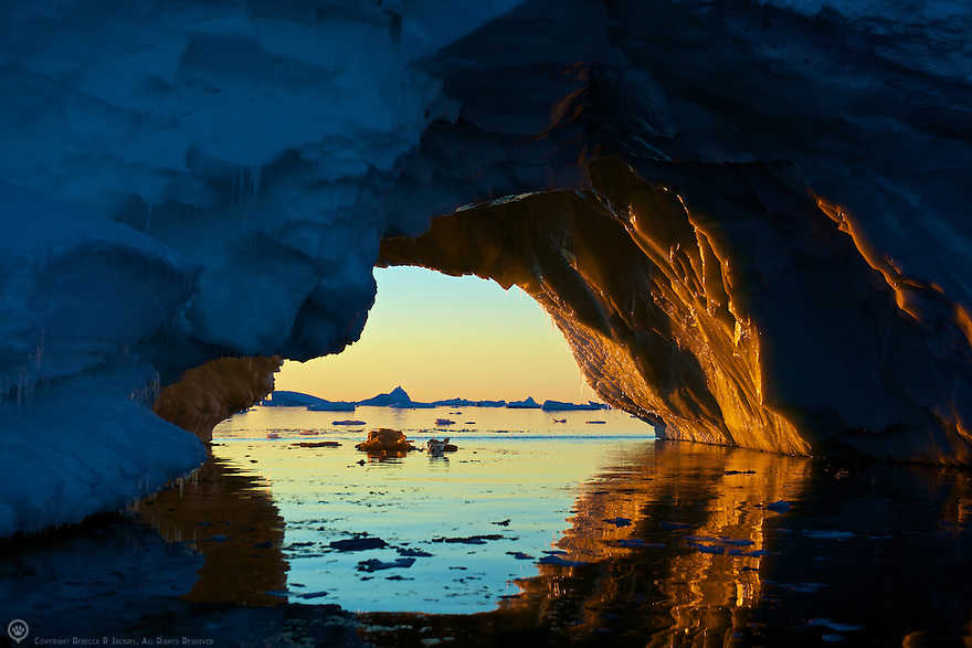 The setting sun illuminates an arch in an iceberg.