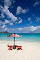 Red striped beach umbrella and chairs at Cinnamon Bay<br /> Virgin Islands National Park<br /> St John, US Virgin Islands