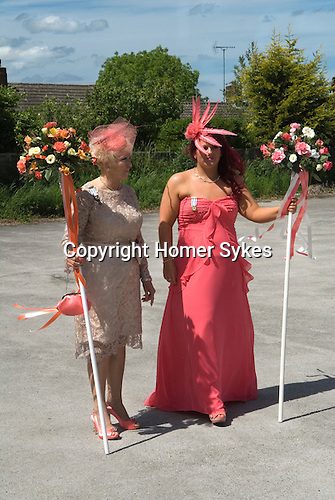 Neston Female Friendly Society Annual Club Walking Day. Neston Cheshire UK 2015. Now knows as the Ladies Club.<br /> <br /> L-R. Mrs Val Hatton and friend Mrs Keri Roberts in full length coral dress, and fashionable feather fascinator. Both women are local Nestonians and walked as children. Mrs Hatton owns a local hairdressers, 'Salon Dene', a 'Ladies Hair Stylists' and Mrs Roberts works along side her. Mrs Hatton has been hairdressing for 53 years.