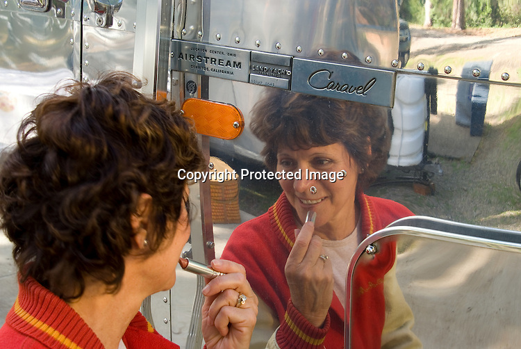 Woman putting on makeup/lipstick by using the reflection of a polished 1969 Airstream Caravel vintage travel trailer.