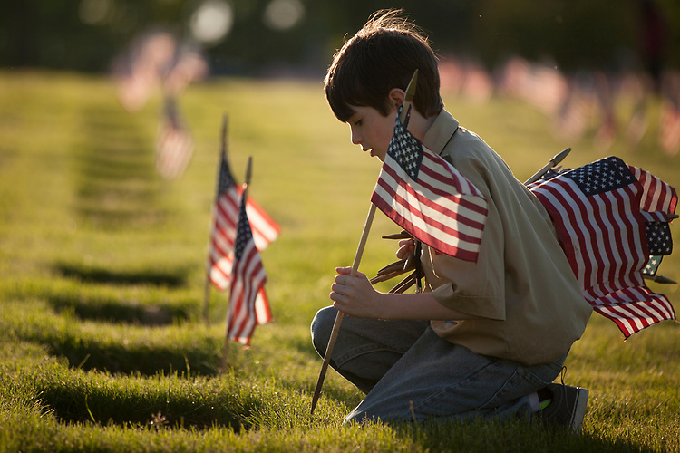Nick Tibbets,11, a Scout from Troop 544, places an American Flag on the headstone of a veteran at Willamette National Cemetery.<br /> Photo by Jaime Valdez