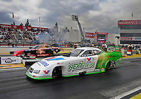 Feb. 12, 2012; Pomona, CA, USA; NHRA funny car driver Jack Beckman (near lane) races alongside Gary Densham during the Winternationals at Auto Club Raceway at Pomona. Mandatory Credit: Mark J. Rebilas-