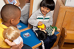 Education preschool first days of school two boys pretend play in family area talking and playing with dolls
