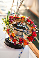 Head flower lei draped over sailboat winch in the morning
