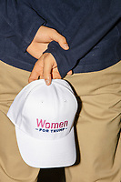 "A man holds a baseball cap reading ""Women for Trump"" while waiting before Donald Trump, Jr., the son of US president Donald Trump, speaks at a 'Make America Great Again!' campaign rally at DoubleTree by Hilton MHT in Manchester, New Hampshire, on Thu., Oct. 29, 2020. The event took place five days before the Nov. 3 presidential election."
