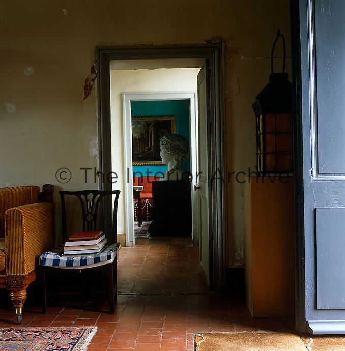 The monument-sized head of an antique goddess is glimpsed through the doorway of an upstairs sitting room