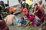 Indian Hindu Pilgrims take a holy bath in the Ganges River in Allahabad for Kumbh Mela Festival.