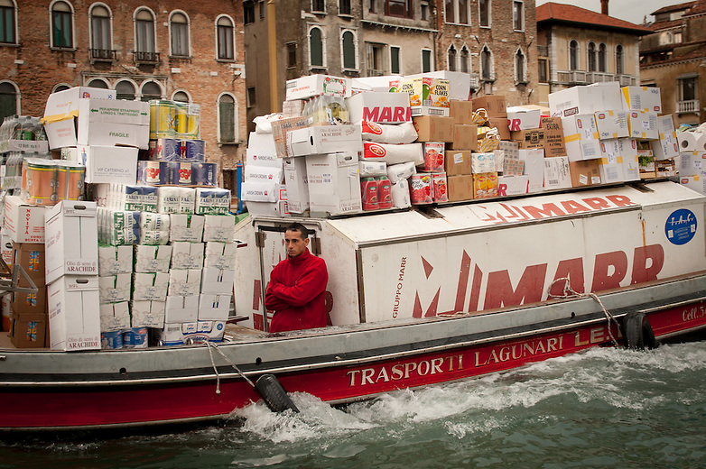 The delivery of goods is challenging in Venice. Private barges transport their goods along the canals of the city loading and unloading from the piers. Barges, fridge-boats, water-ambulances, funeral boats, firemen's boats, garbage boats are part of each Venetian's everyday life.