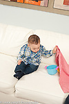 9 month old baby boy sitting on couch lifting cloth to find hidden toy Piaget object permanence