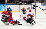 Sochi, RUSSIA - Mar 11 2014 -  Derek Whitson stops to pick up the puck as Canada takes on Czech Republic in Sledge Hockey at the 2014 Paralympic Winter Games in Sochi, Russia.  (Photo: Matthew Murnaghan/Canadian Paralympic Committee)