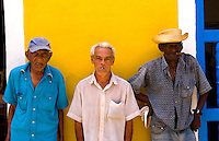 Local old men with cigar against bright yellow wall of building of the old colonial city of Trinidad in Cuba