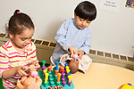 Education Preschool 3 year olds boy and girl playing separately with dolls pretend play feeding them bottles