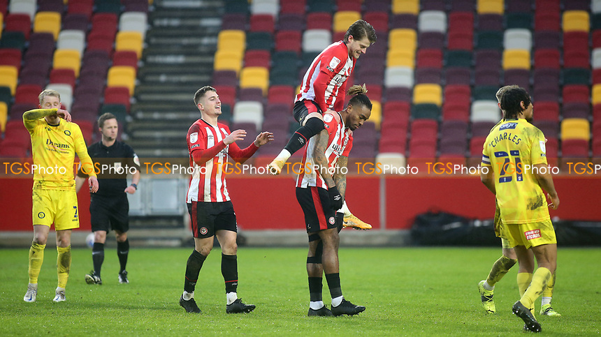 Mathias Jensen leaps onto the back of Ivan Toney to celebrate Toney scoring Brentford's fourth goal from the penalty spot during Brentford vs Wycombe Wanderers, Sky Bet EFL Championship Football at the Brentford Community Stadium on 30th January 2021