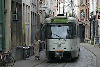 A woman boards tram line 10 on Wolstraat in Antwerp, Belgium