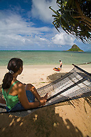 Young woman in hammock at beach and man with kayak, Chinaman's Hat in background, Kualoa Regional Park, East Side of Oahu