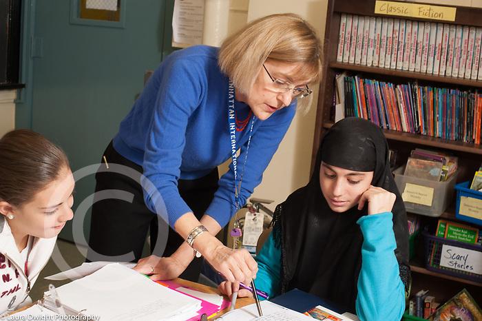 Education High School female teacher leaning in to explain something to female student