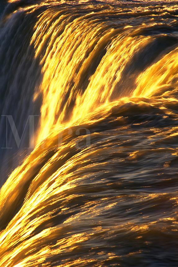 Canada, Ontario, Niagara Falls, close-up of waterfalls with golden sunlight  highlighting the water