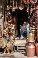 Nepal, Kathmandu.  Vendor of Brass Hindu and Buddhist Decorative Items and Utensils Reading the Newspaper.