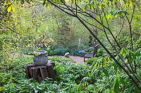 Gravel path to private bench in spring woodland secret garden, Boninti Garden, Virginia
