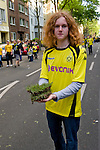 In the stadium Signal-Iduna-Park in Dortmund fans celebrated a party because of the title win of their favorite soccer club BVB 09 in the German Premium League. Here a fan presents his trophy, a piece of the turf, on his way home.
