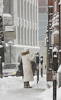 Montreal (Qc) CANADA - December 3rd 2007-.A woman feed a parking meter in Old-Montreal while.Heavy snow fall on Montreal, more than 30cm is expected...photo : (c) ROUSSEL - Images Distribution.